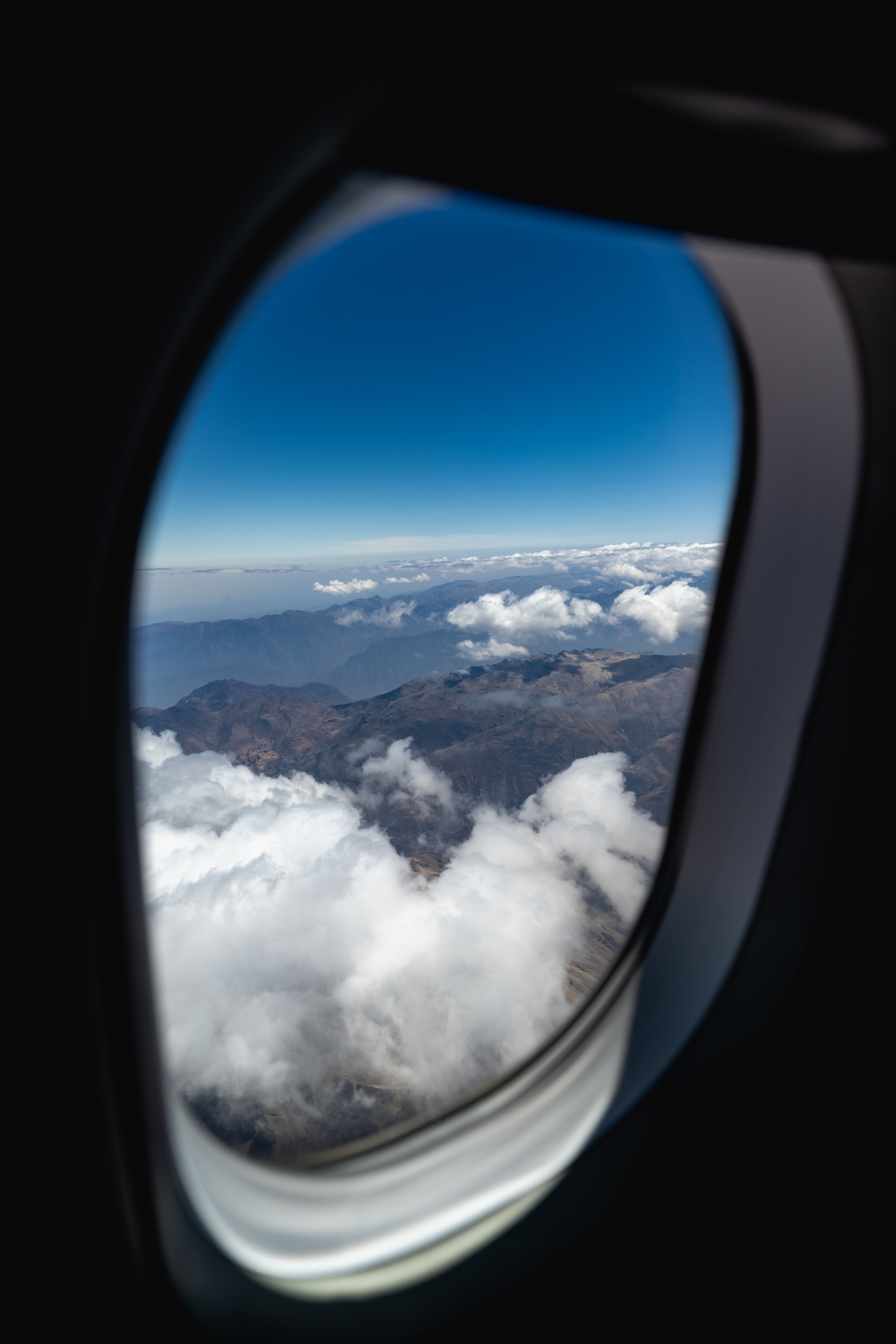 Mountains And Clouds Outside Of An Airplane Window Free Stock Photo