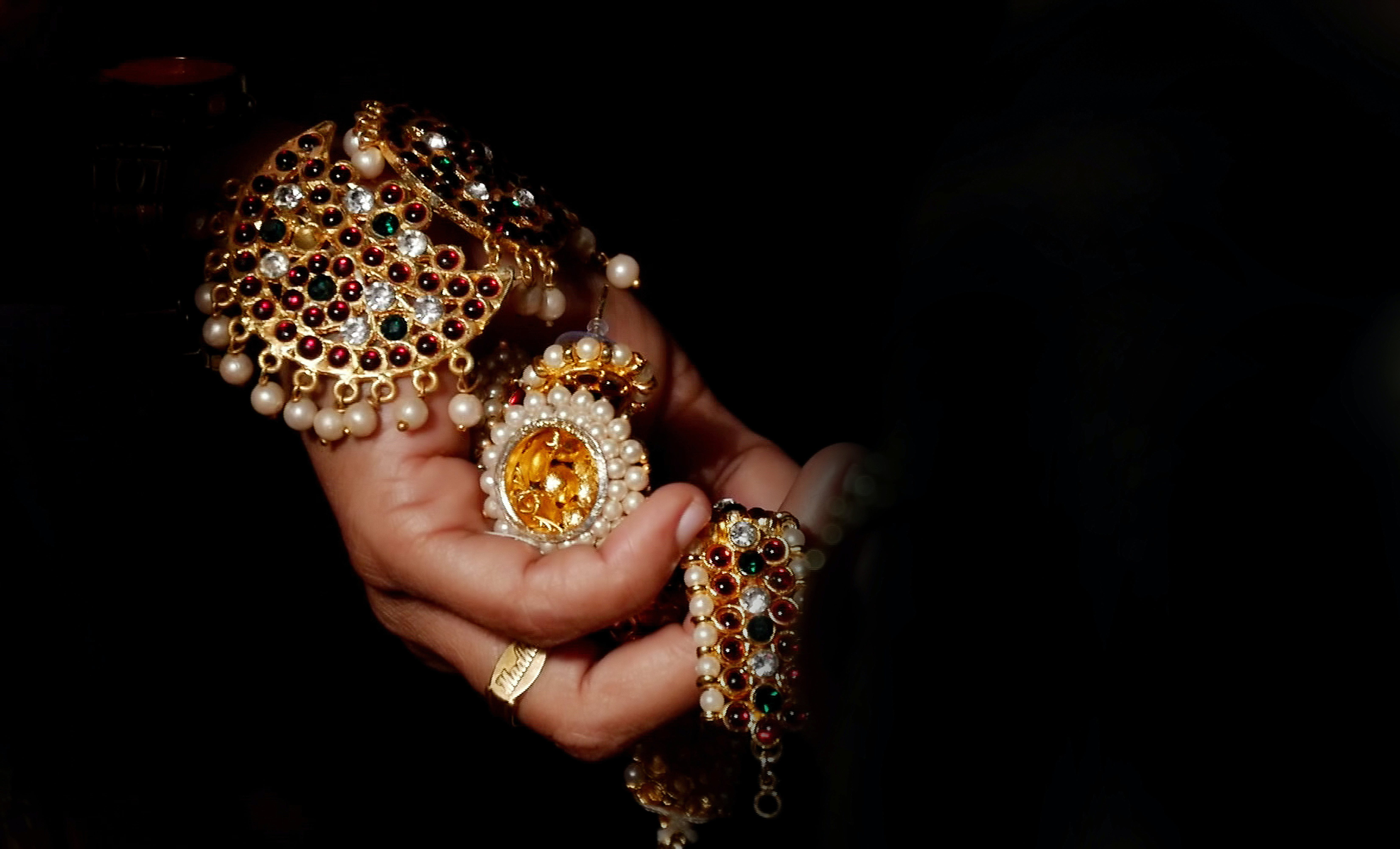Person Holding Gold-colored and White Jewelry