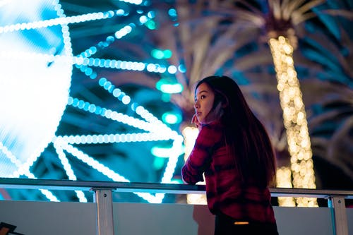Photo of Woman in Black and Red Plaid Shirt Leaning on Metal Railing During Nighttime