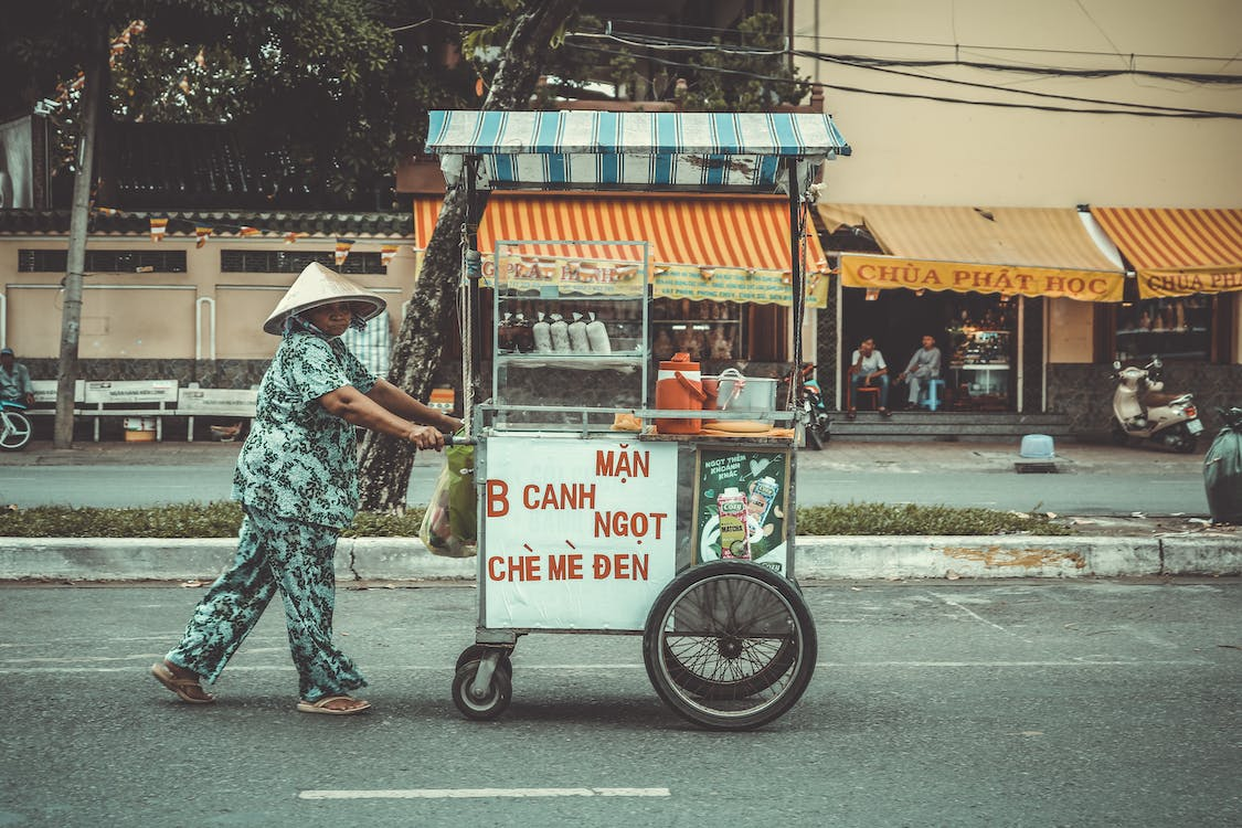 Person Pushing Food Cart On Road