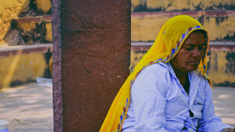 Woman Wearing Yellow Headscarf Sitting Beside Brown Concrete Column