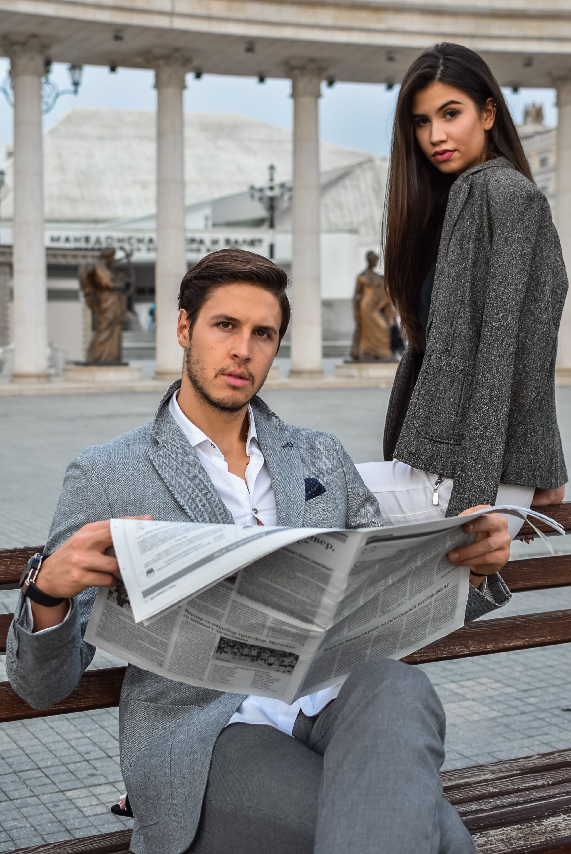 Man Sitting On Bench While Holding Newspaper