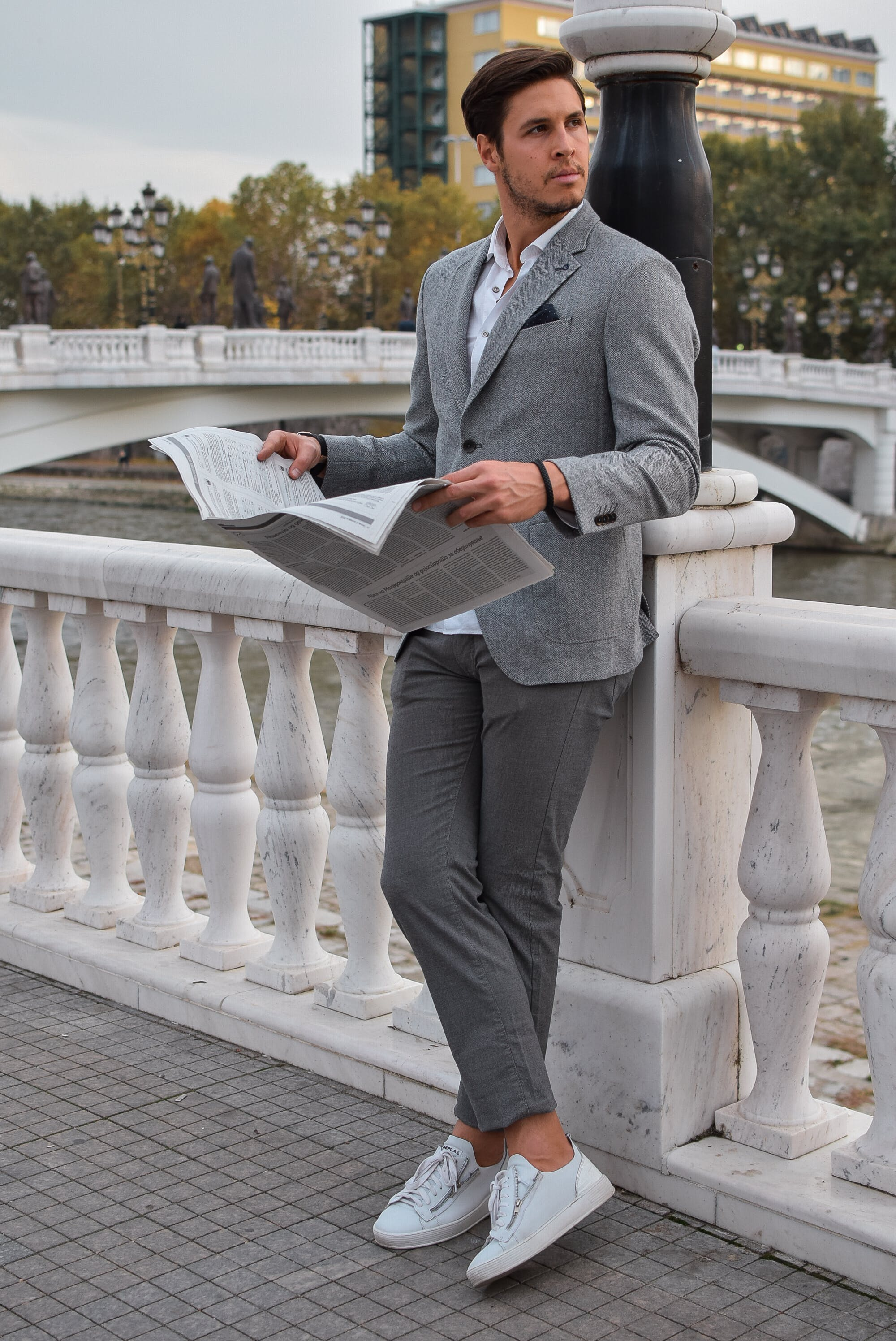 Person Holding Newspaper Wearing Gray Blazer