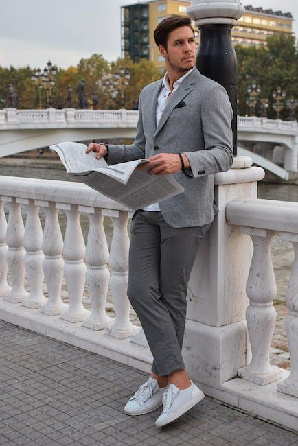 Person holding newspaper wearing gray blazer