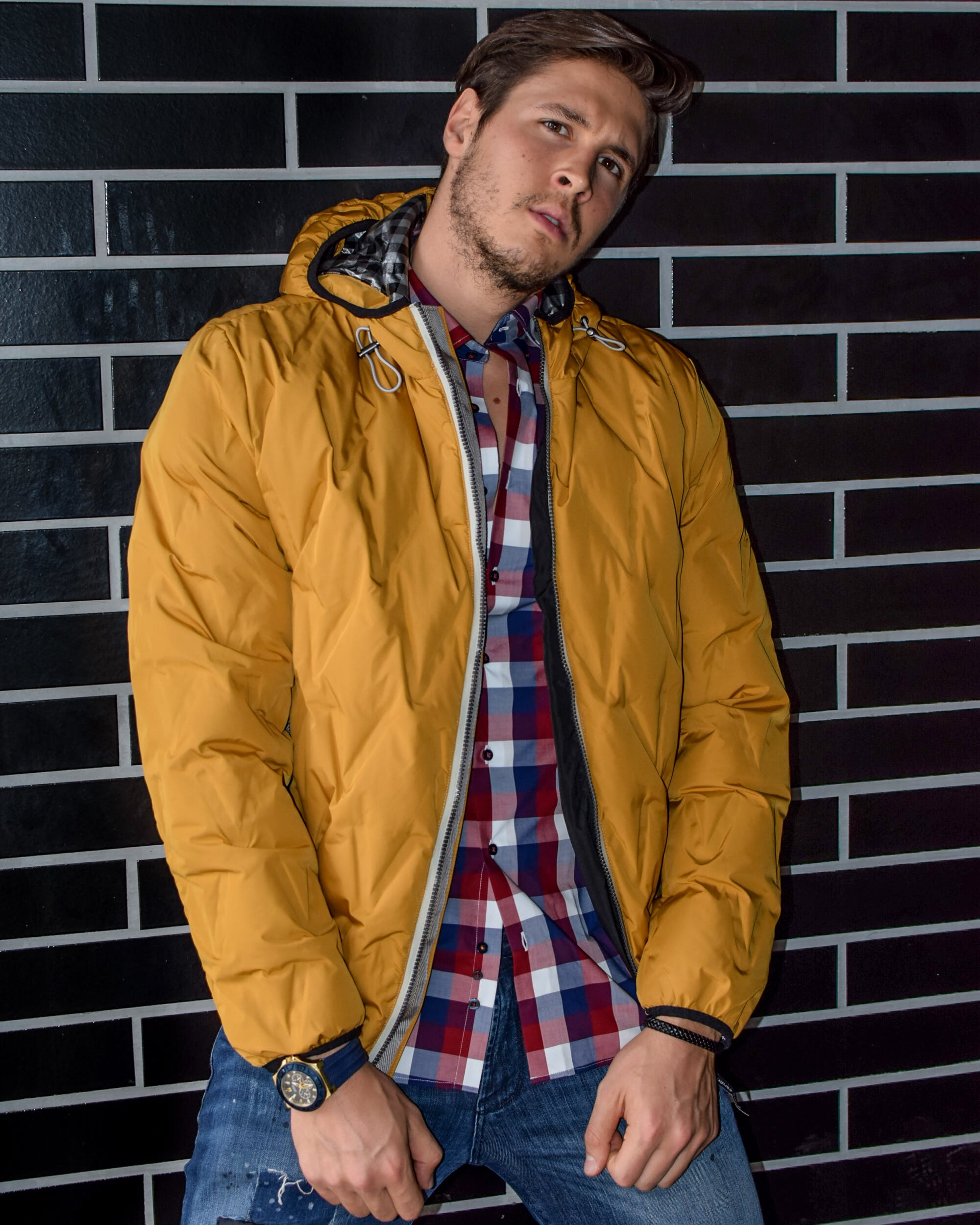 Man Wearing Yellow Zip-up Jacket Leaning on Brown Brick Wall