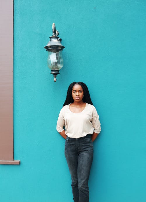 Woman Standing Against Teal Wall Near Sconce