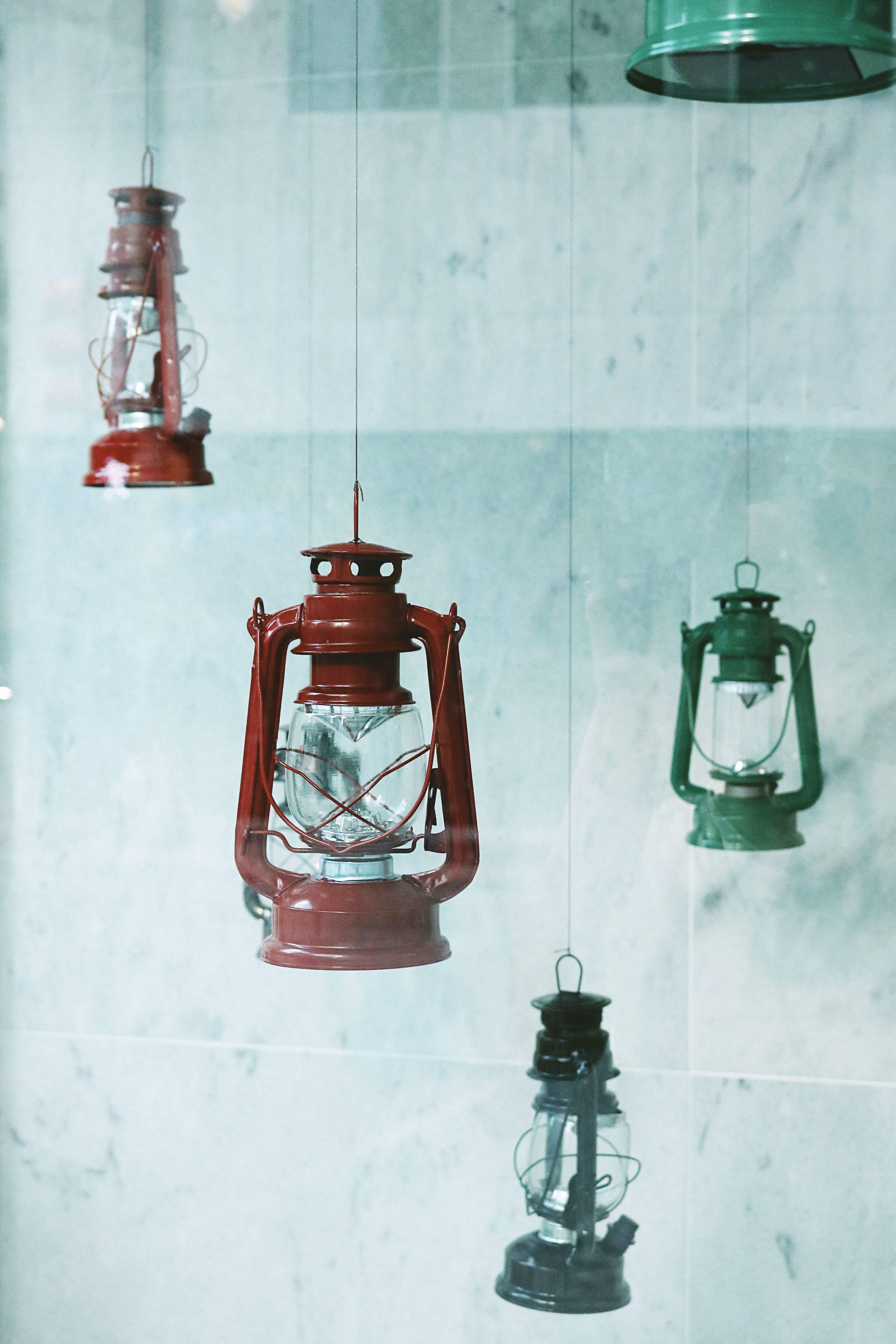 Four Assorted-color Metal Gas Lanterns Hanging Near Tile Wall