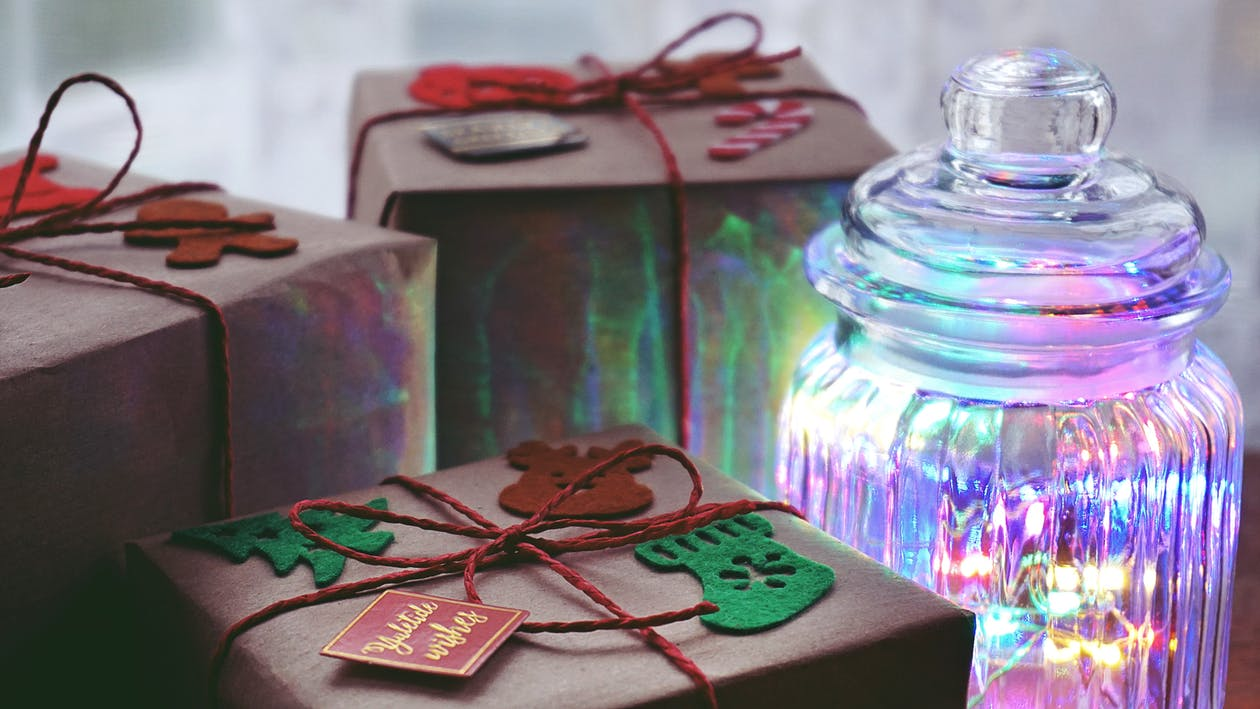 Close-Up Photo of Three Brown Gift Box Beside Clear Glass Container