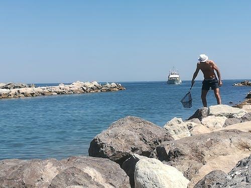 Fotos de stock gratuitas de cerca del mar, hombre en el mar, velero