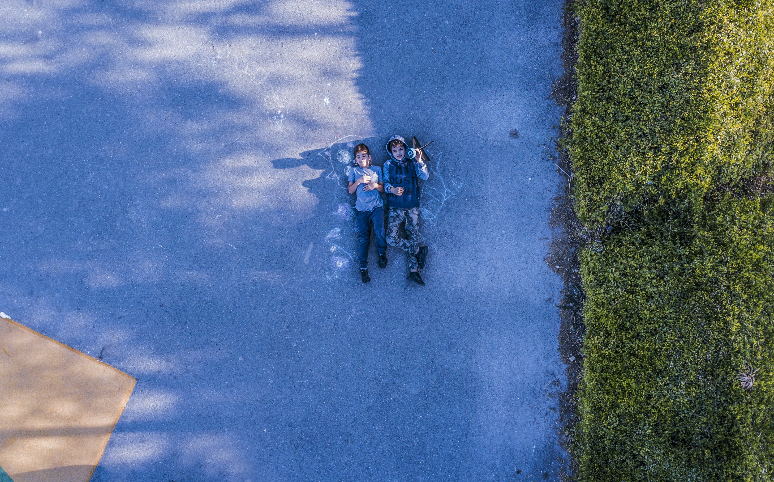 Photo of Two Person Lying on Road Near Green Grass Field