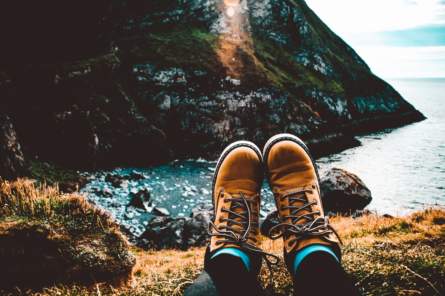 A person is wearing a nike hiking boots while sitting near the ocean