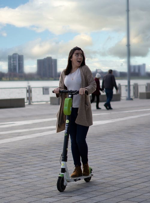 Full body of young thrilled female riding modern scooter on urban street with people under cloudy sky on blurred background