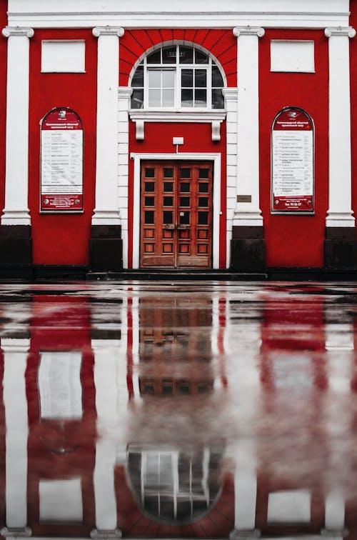 Closed Brown Wooden Door With Reflection on Concrete Wet Floor