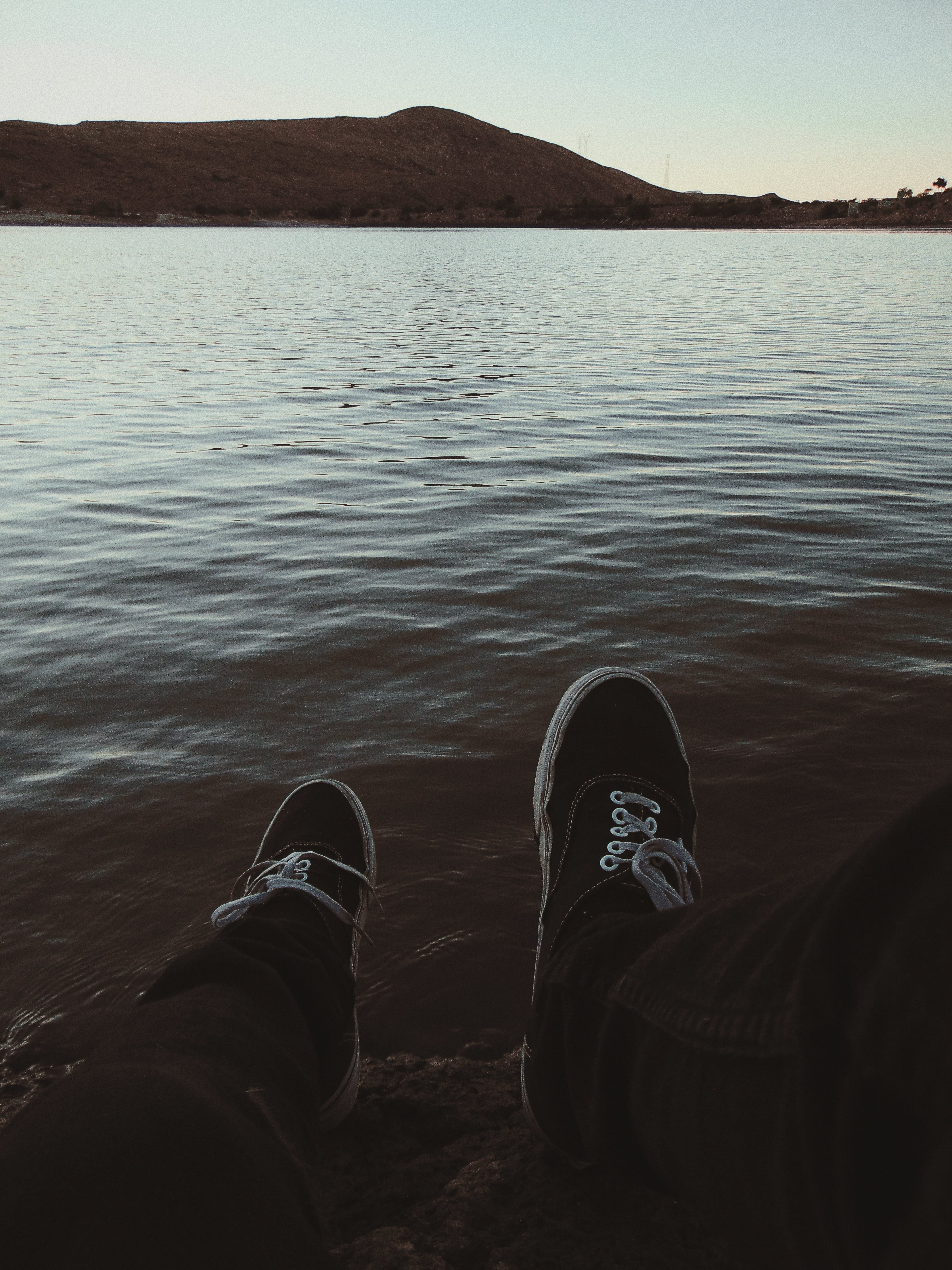 Person Wearing Sneakers Sitting in Front of Ocean