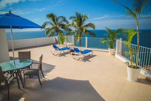 Blue Loungers on Beige Balcony Beside Sea Landscape Photography