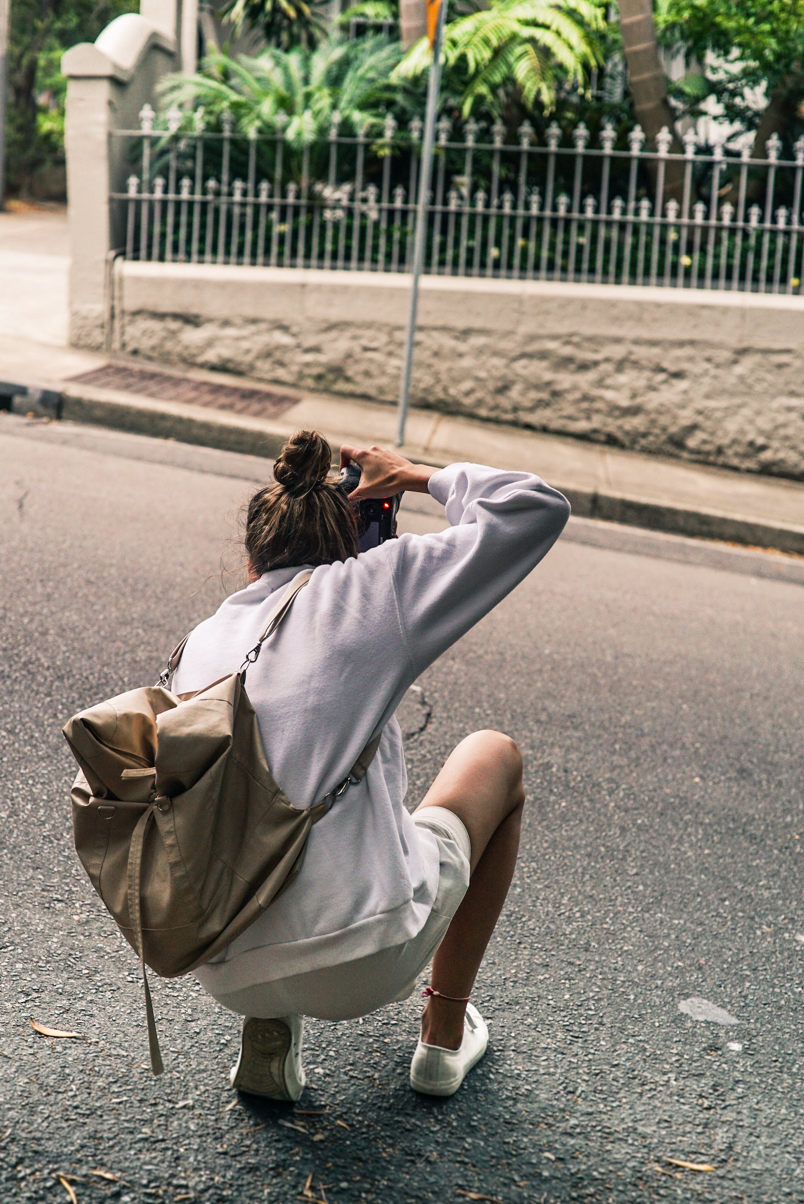 Person Kneeling on Road While Taking Picture