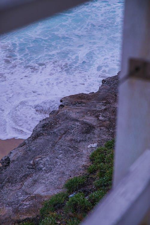 Bemoste rotsen, daglicht, golven