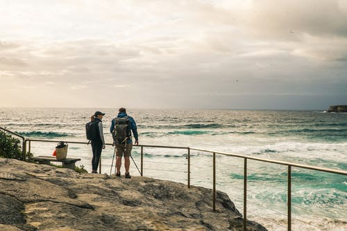Man and Woman Standing on the Rocky Edge With Hand Rail Beside Ocean