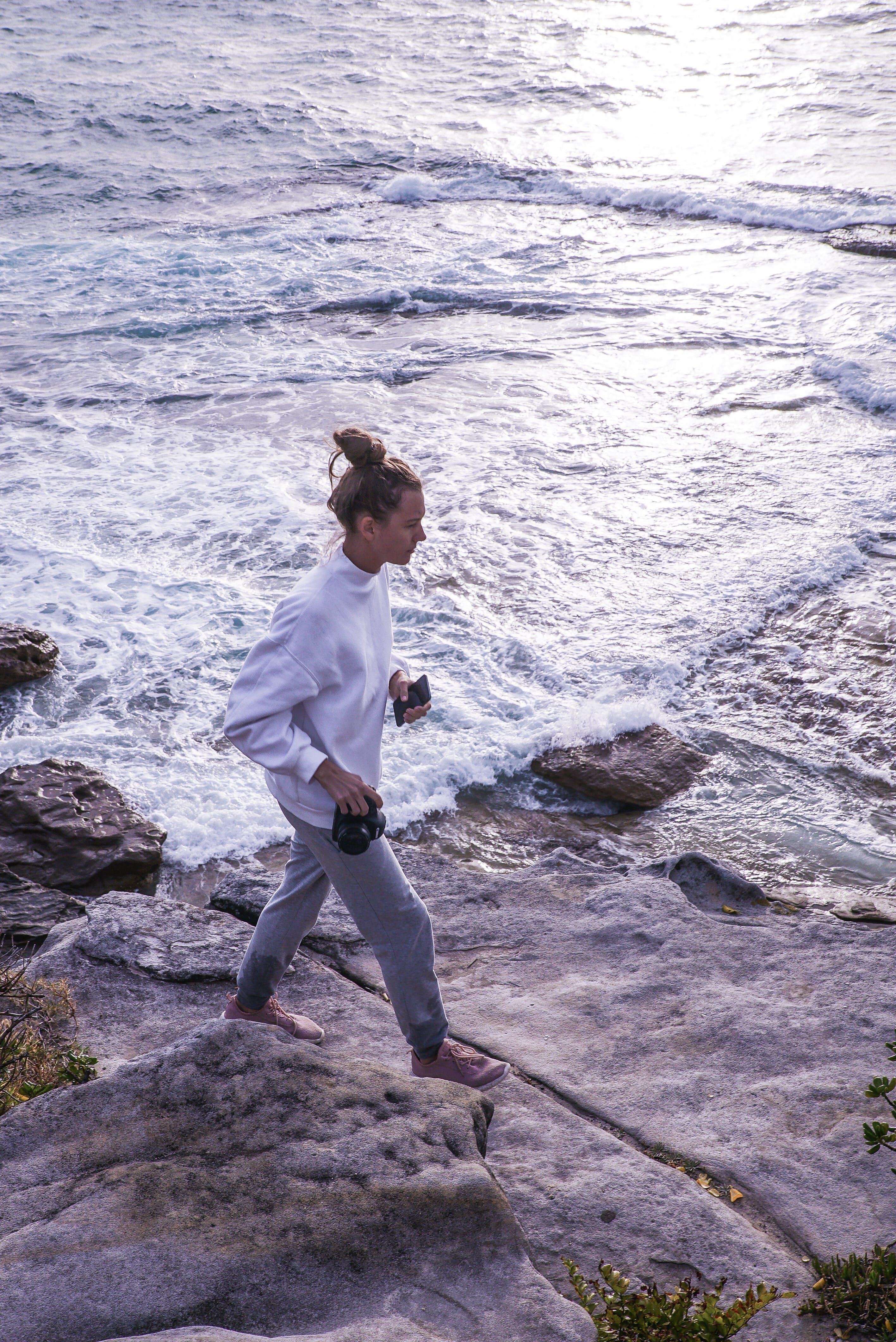 Photo of Woman Walking Near Ocean