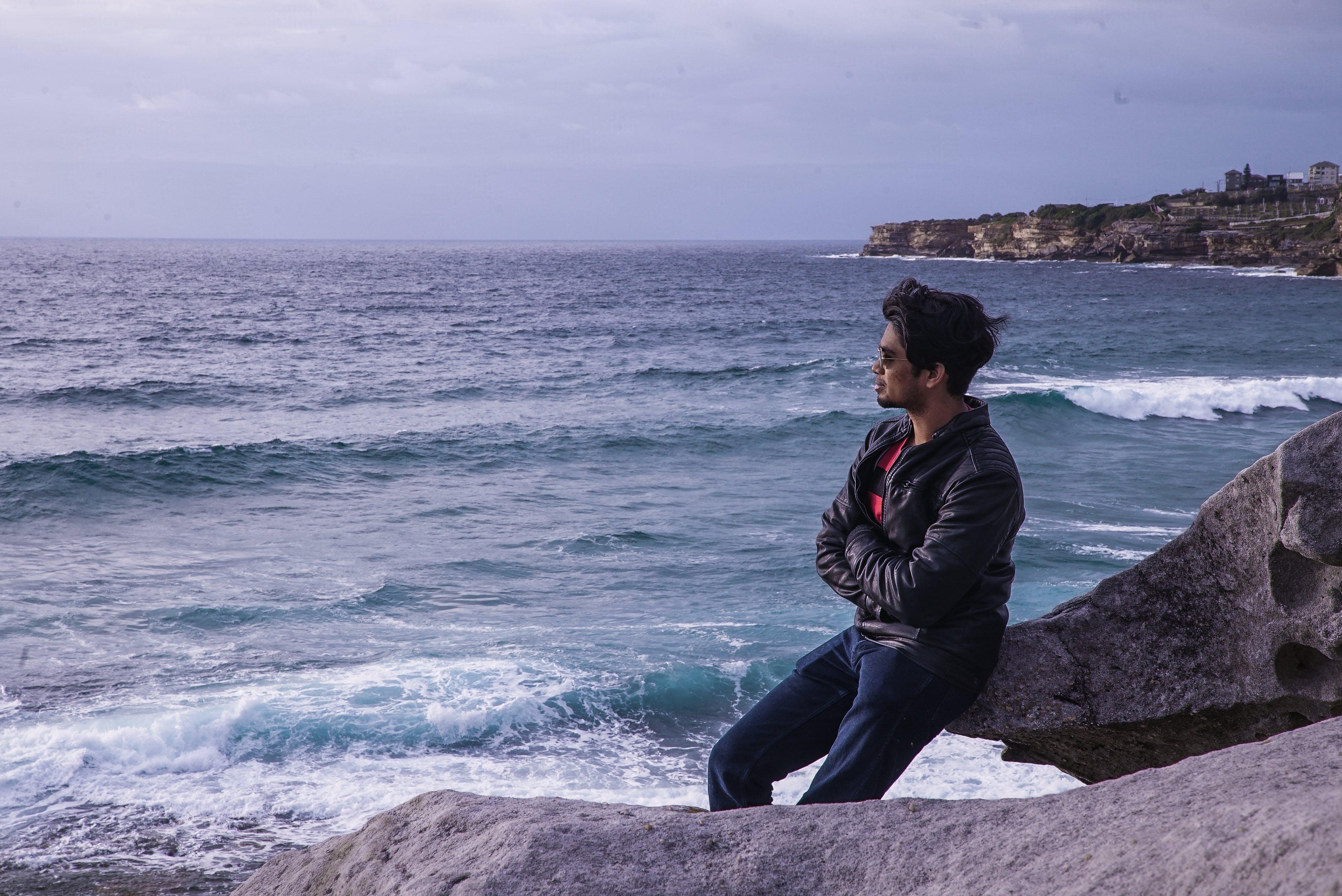 Man Leaning on Rock Near Beach Shore