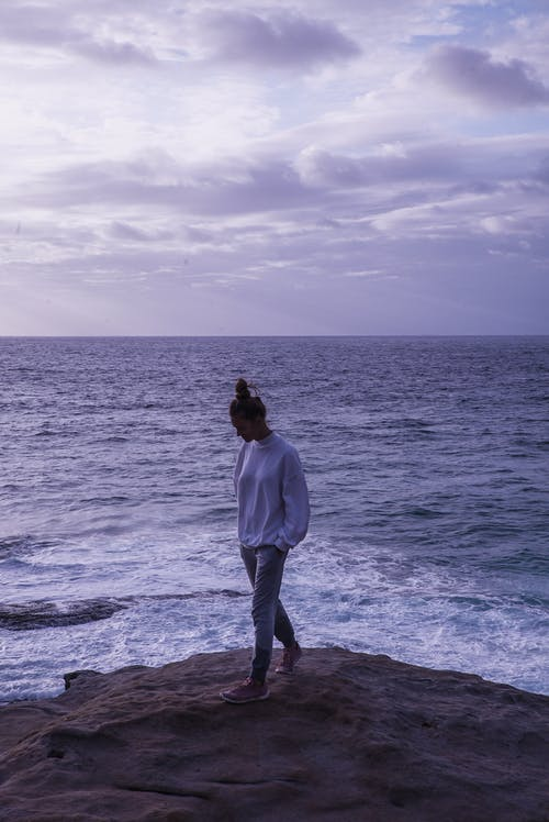 Photo of Woman Standing On Rock Near Ocean