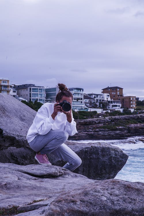 Woman Sitting on Rock While Taking Photo