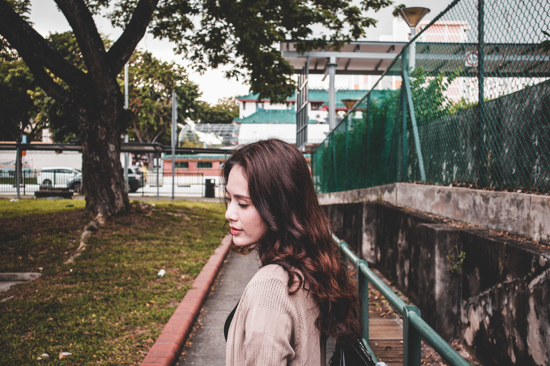 Woman Wearing Brown Cardigan Walking on Park Near a Green Tree