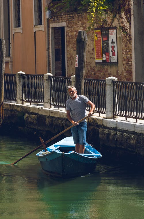 Man Riding a Blue Row Boat