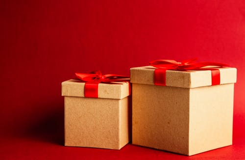 Two Brown-and-red Gift Boxes on Red Surface