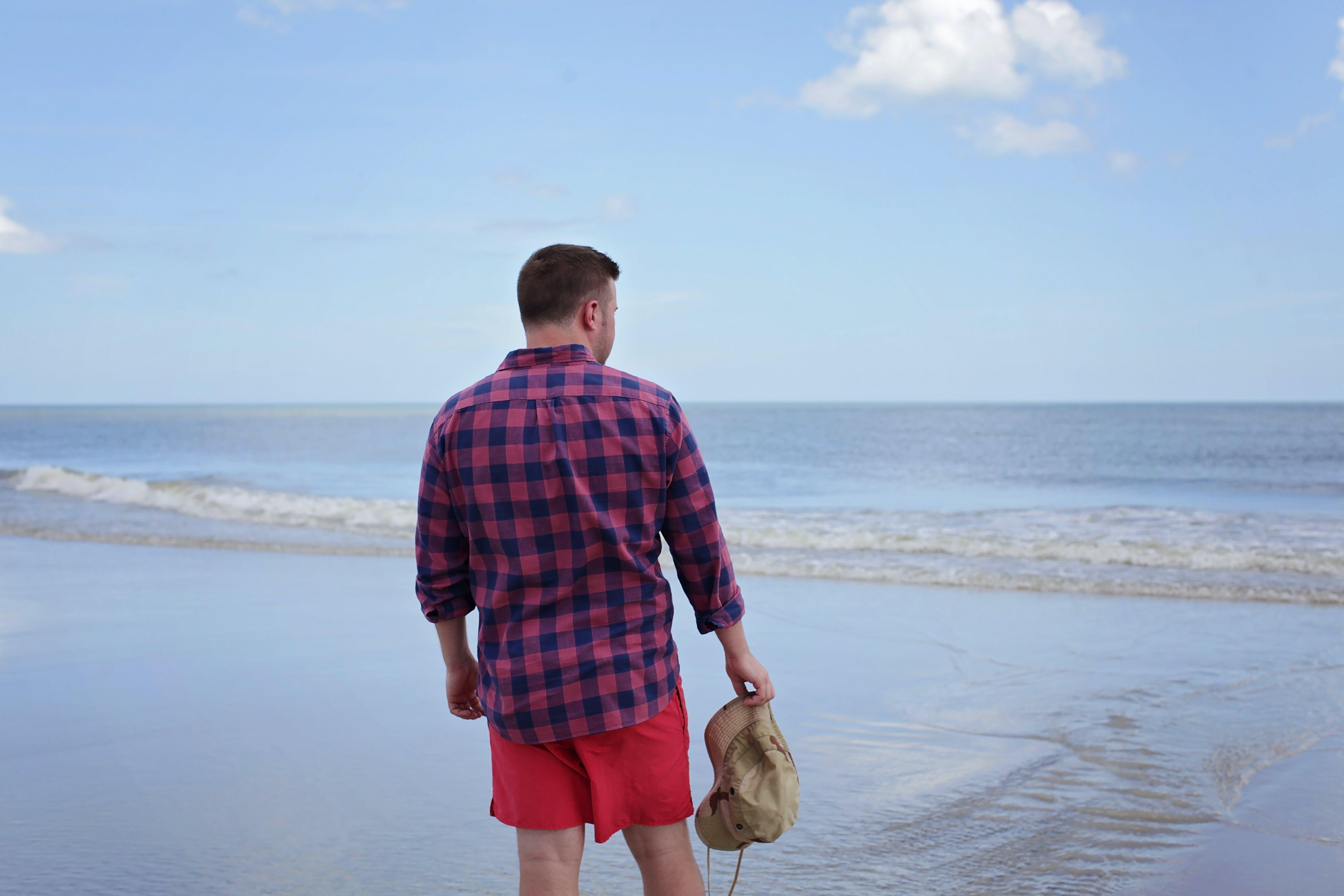 Man Holding Brown Hat Facing Beach