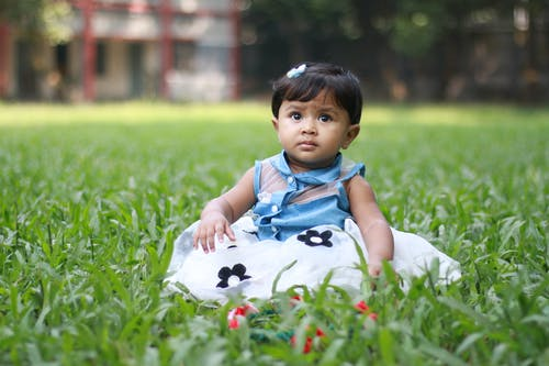 Photo of Baby Sitting On Grass