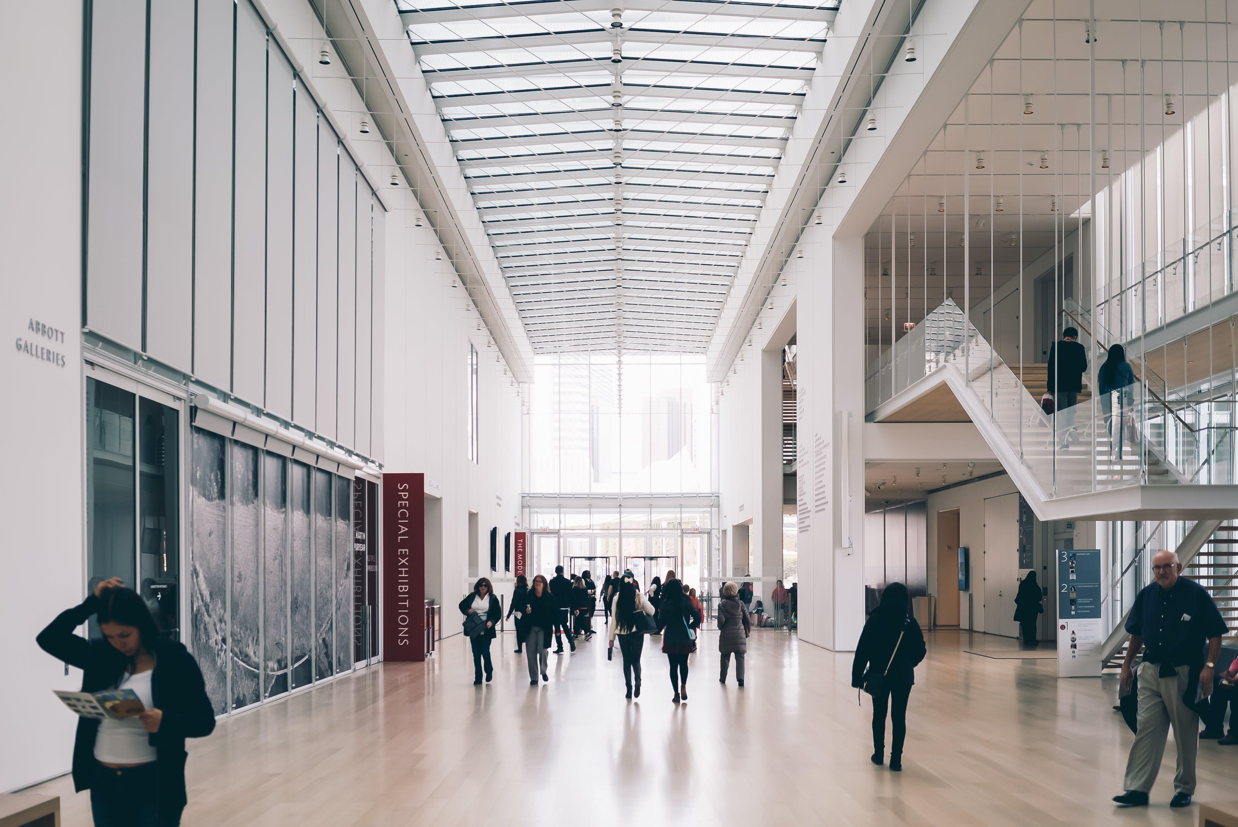 People Along Hallway of Concrete Building