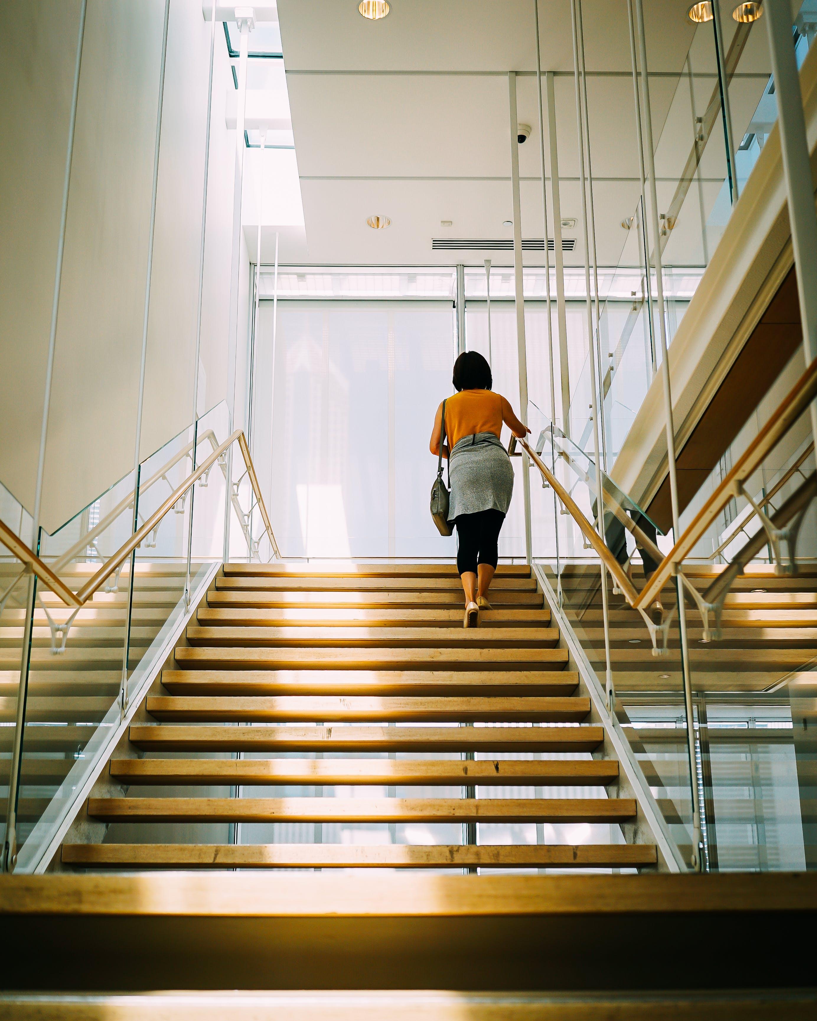 Woman Walking on Brown Stair