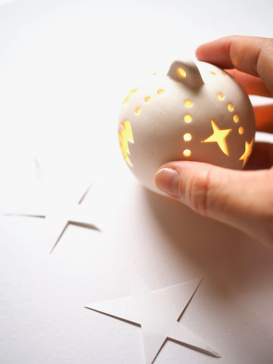 Person Holding White and Brown Ornament