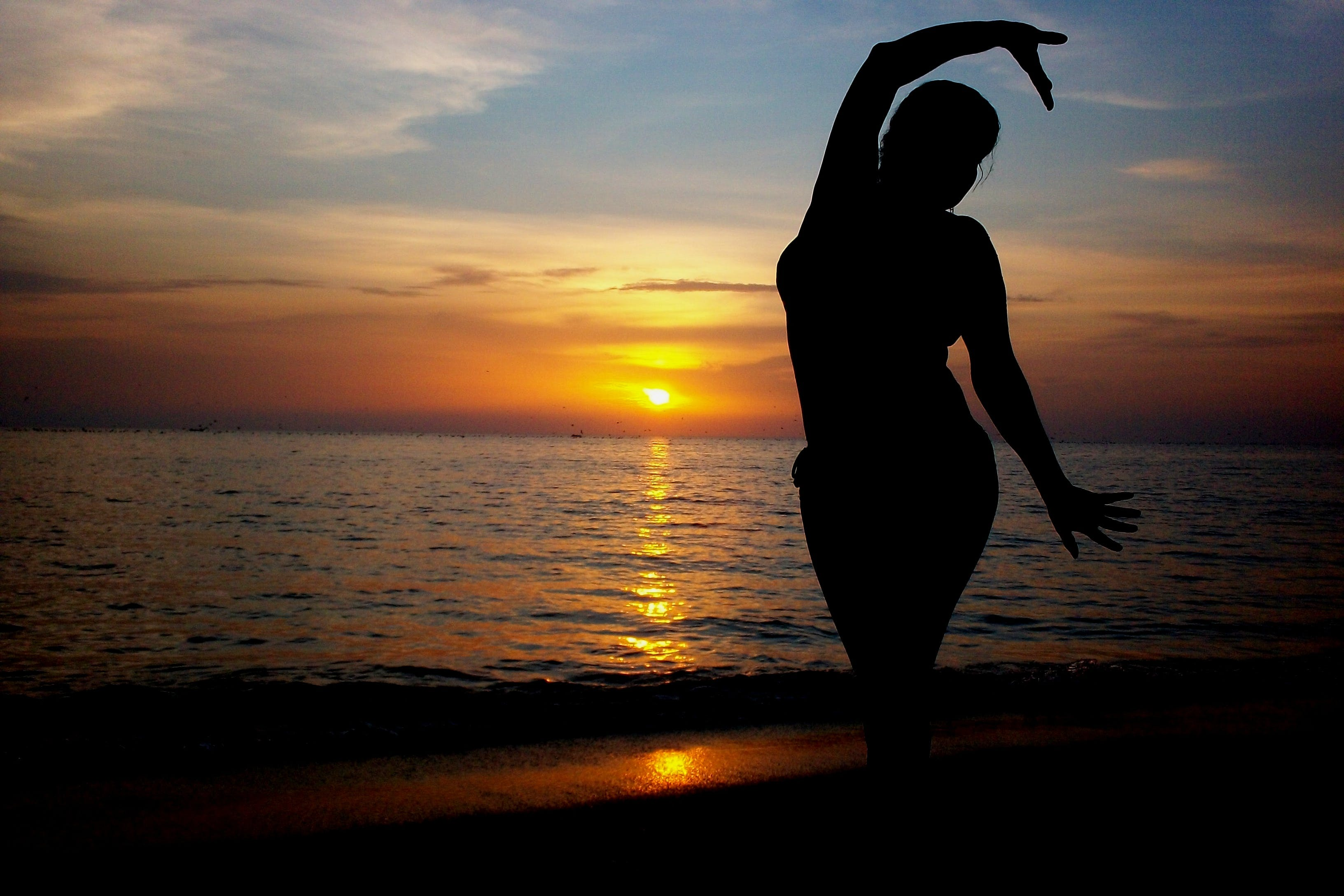 Silhouette of Standing Woman on Seashore during Sunset