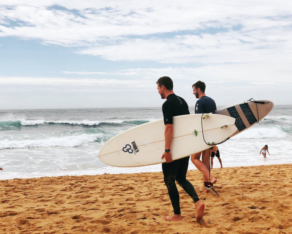 Two Men Carrying Surfboards Near Seashore