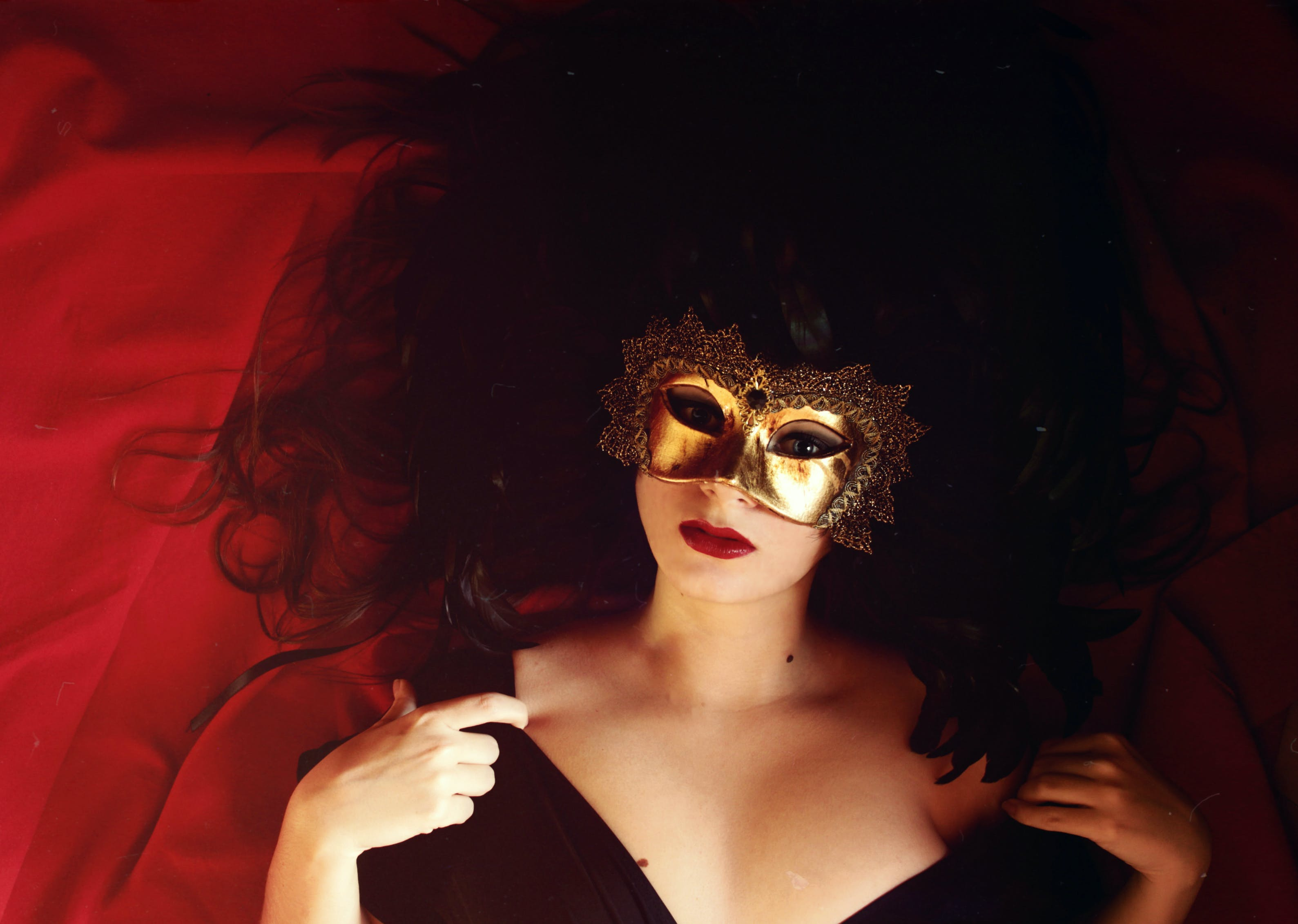 Woman Laying On Red Textile Wearing Gold Mask