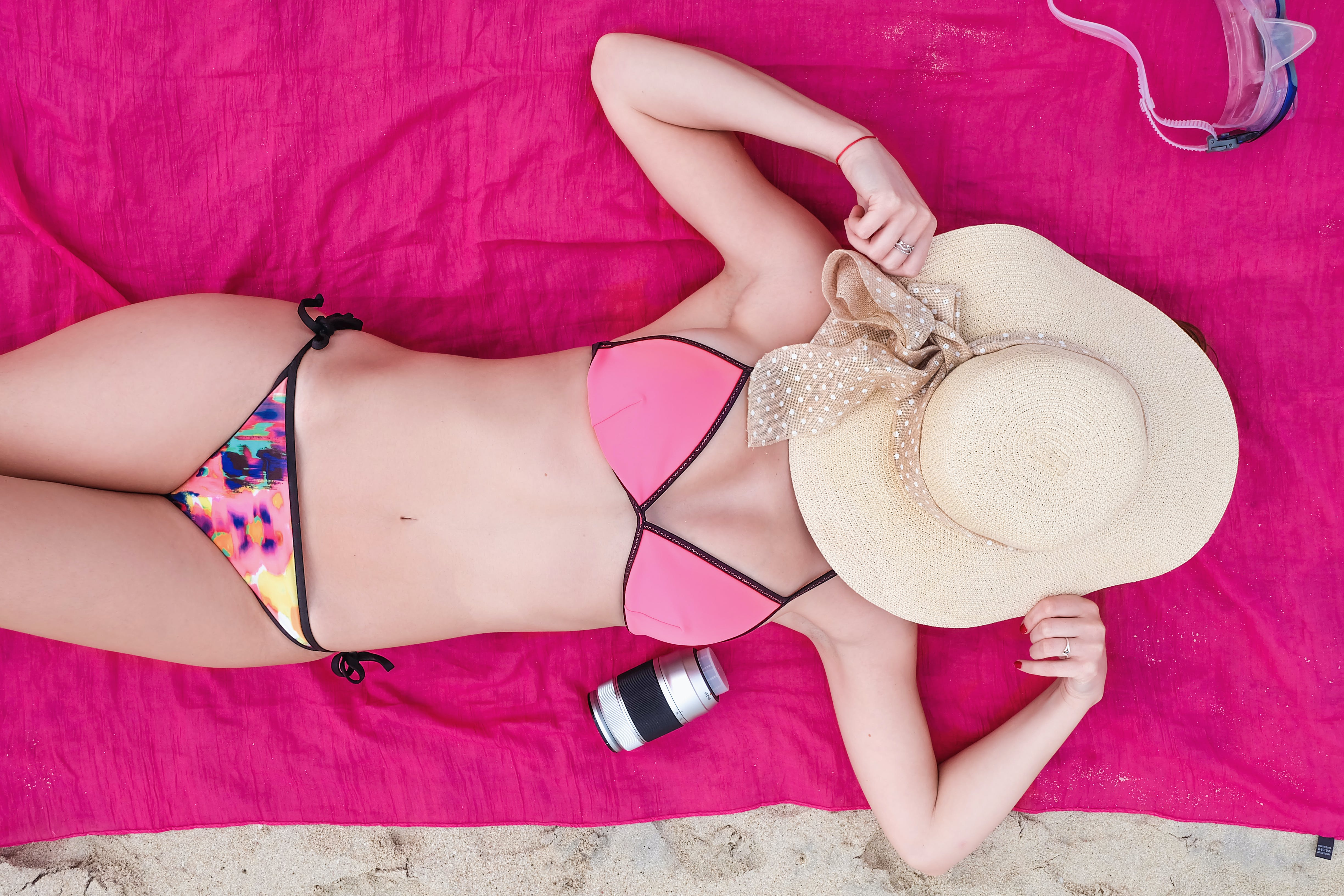 Woman Laying On Pink Towel Wearing A Bikini