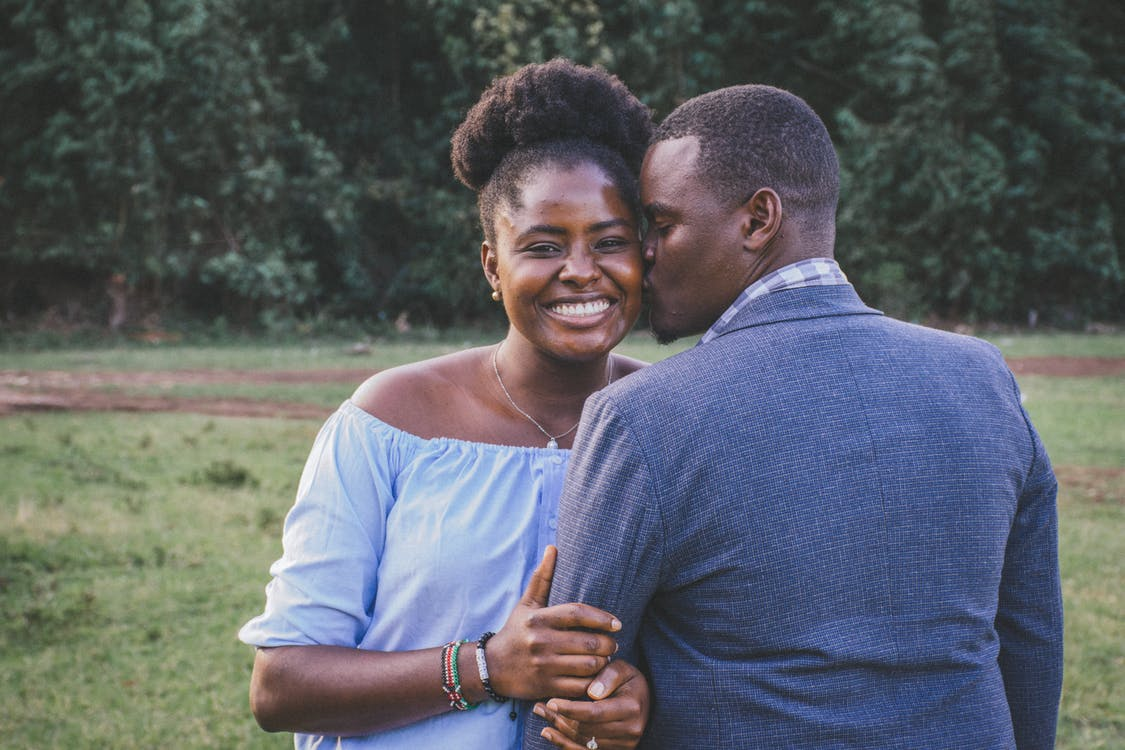 Man Kissing Left Cheek of Smiling Woman