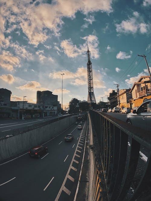 Безкоштовне стокове фото на тему «автомобілі, будівлі, вежа, дорога»