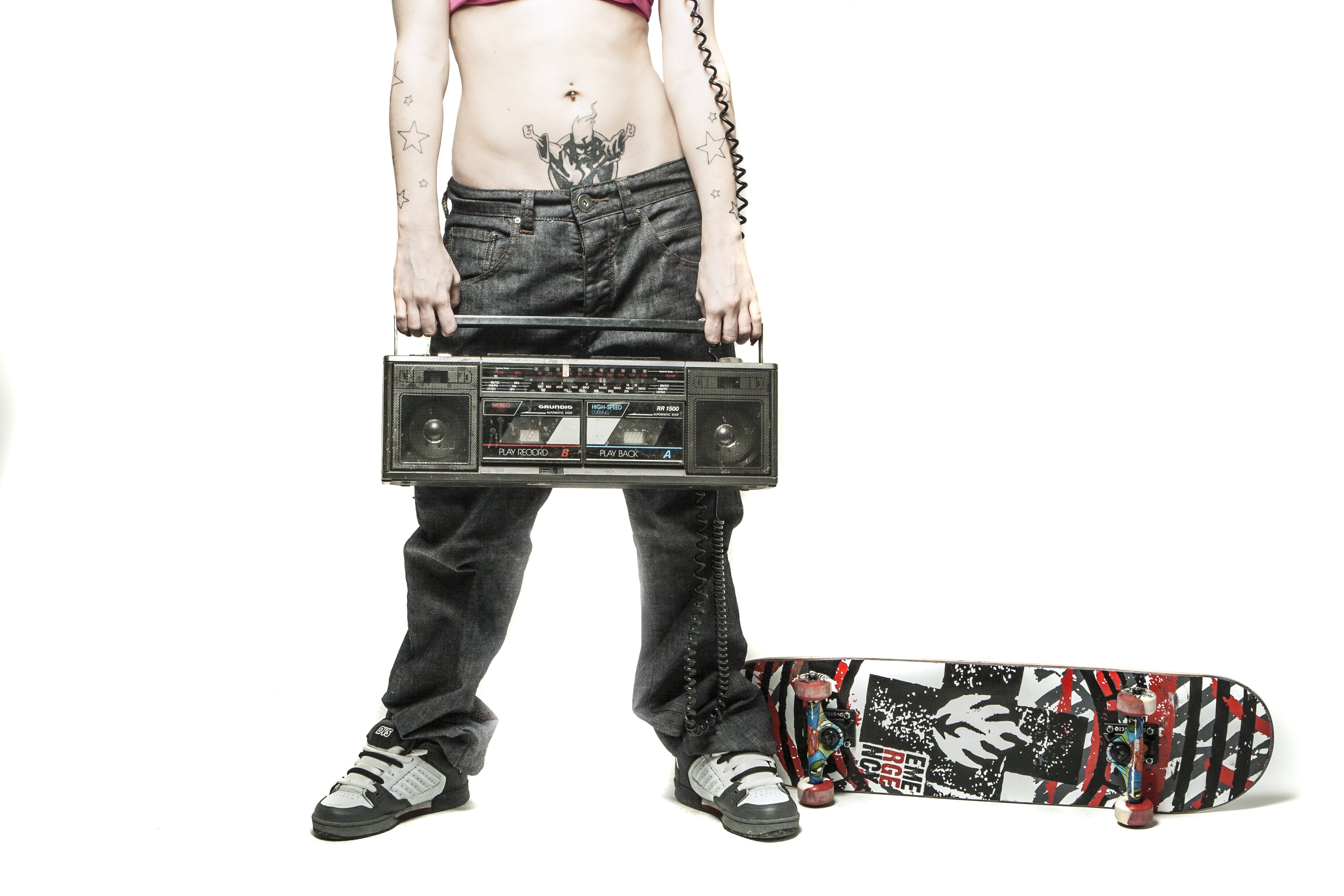 Woman Holding Boombox Near Skateboard