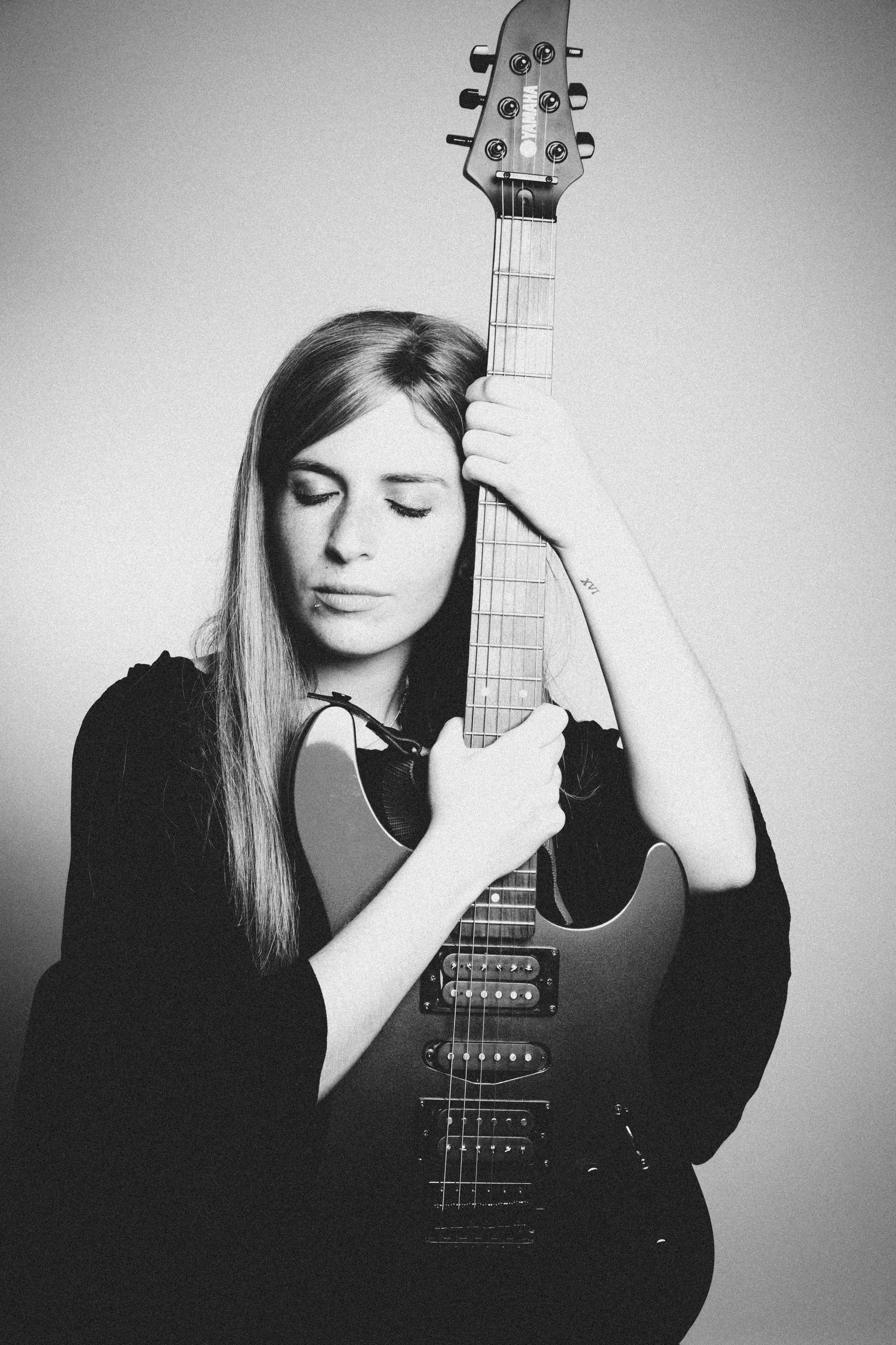 Grayscale Photography of Woman Holding Electric Guitar