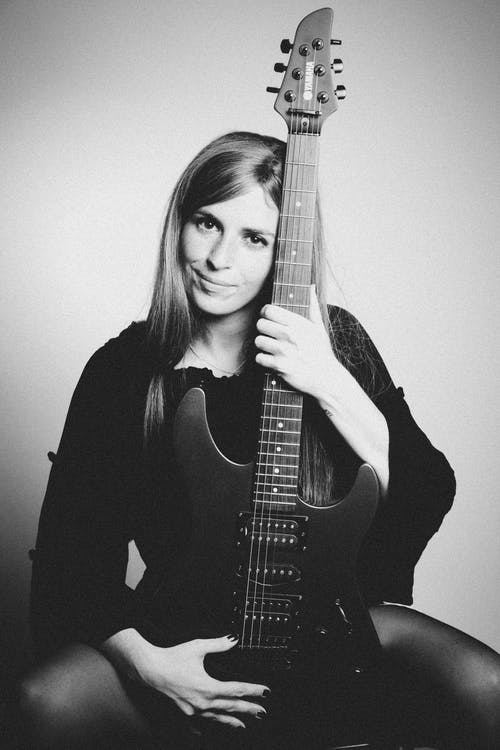 Grayscale Photo Of Woman Holding Guitar While Sitting