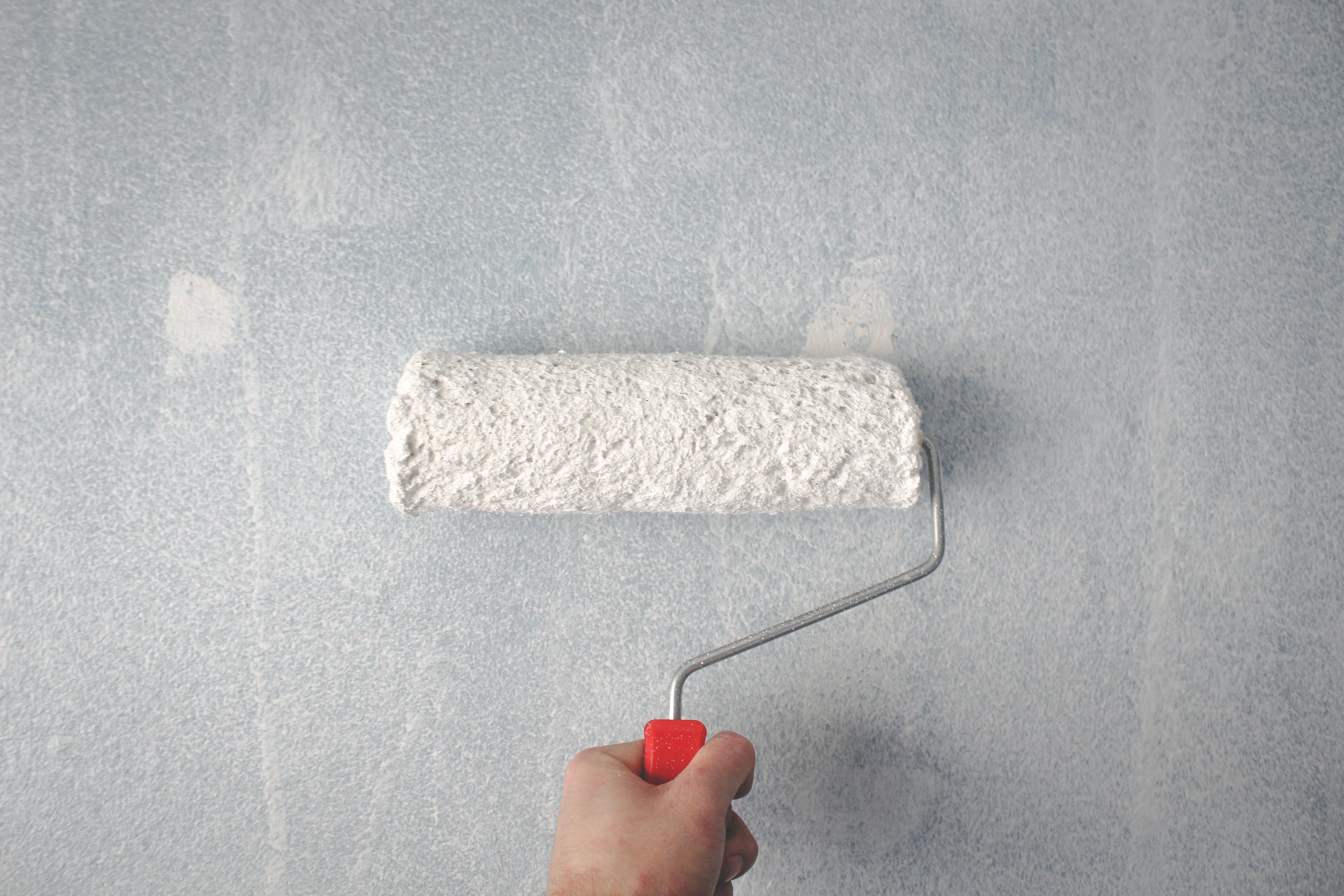 Foto d'estoc gratuïta de corró de pintura, mà, mur, pintant