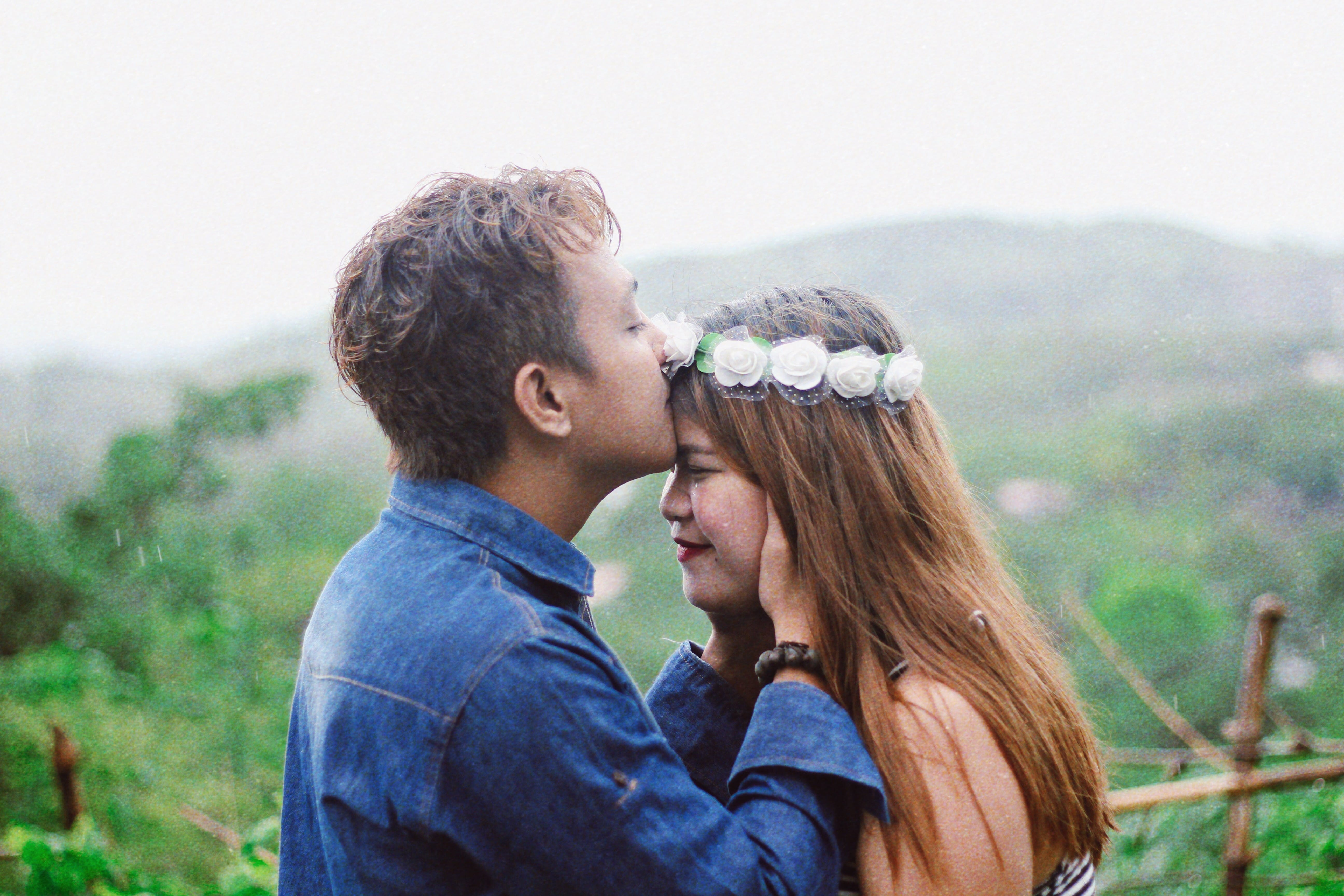 Man Wearing Blue Denim Jacket While Kissing Woman's Forehead