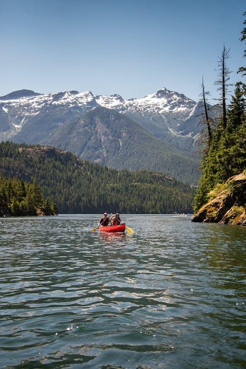 两个人在红色皮划艇漂浮在蔚蓝的天空下山附近的水体上