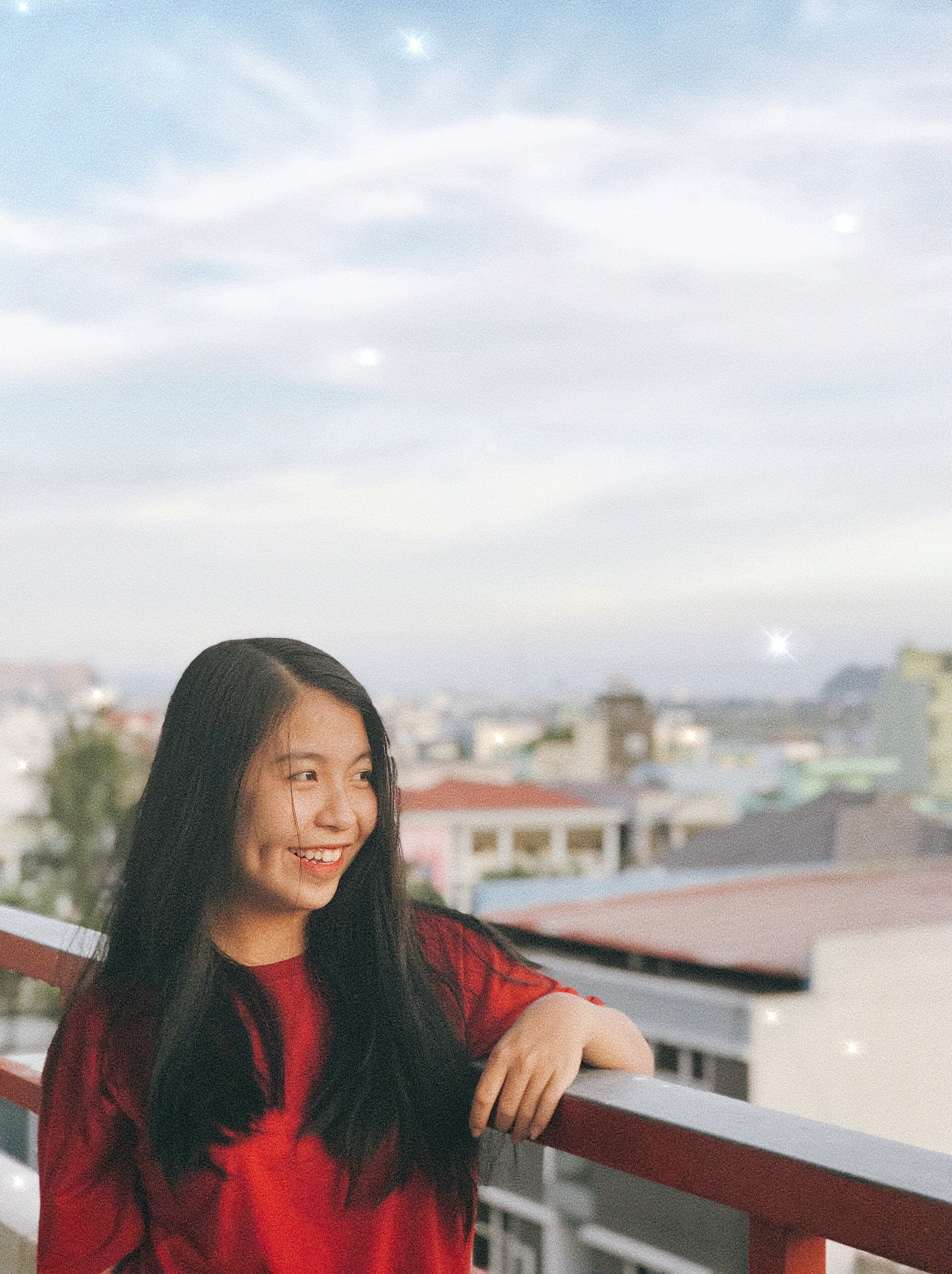 Smiling Woman Leaning on Balcony Fence
