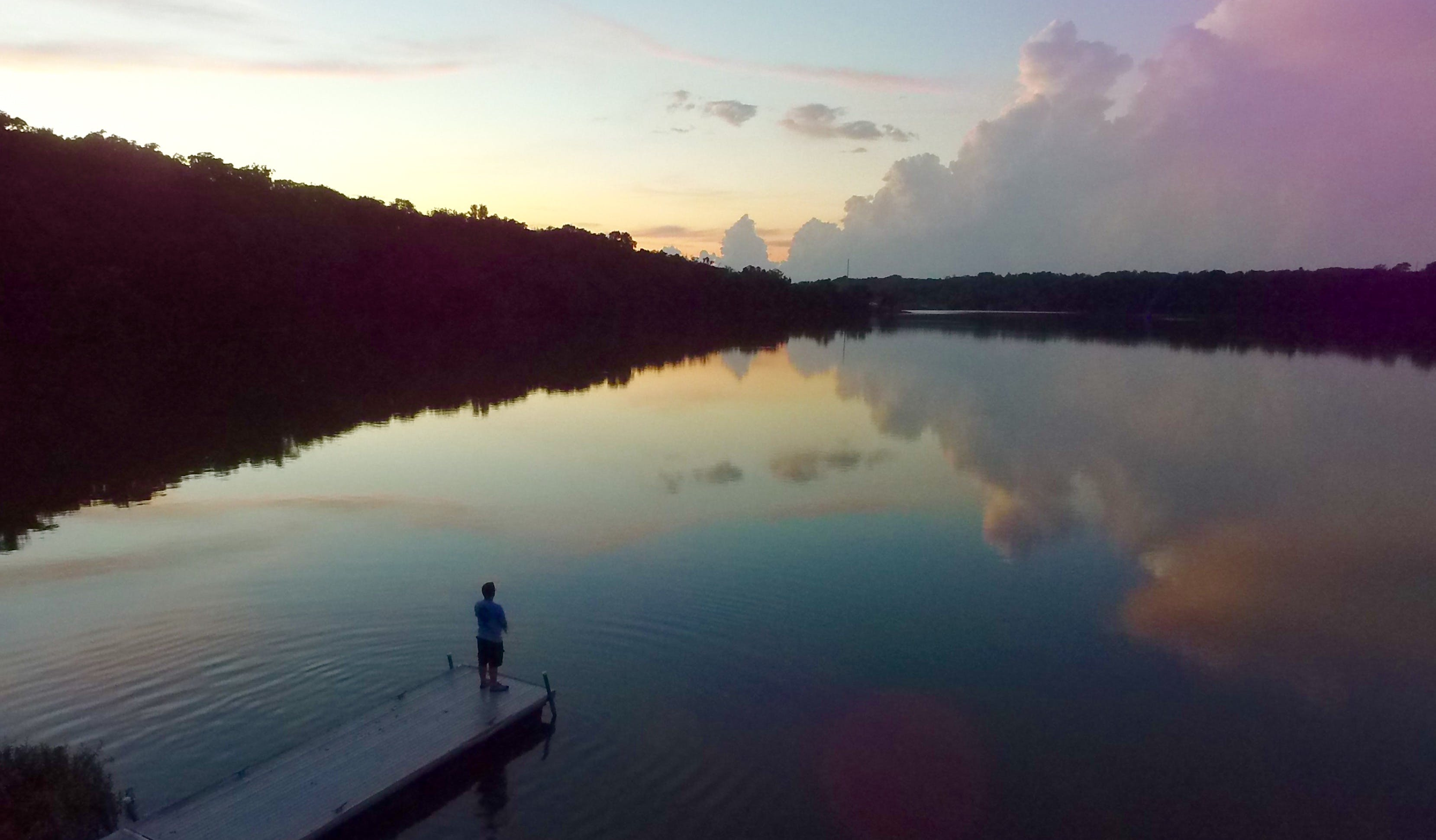 Man Standing on River Dock during Sunset