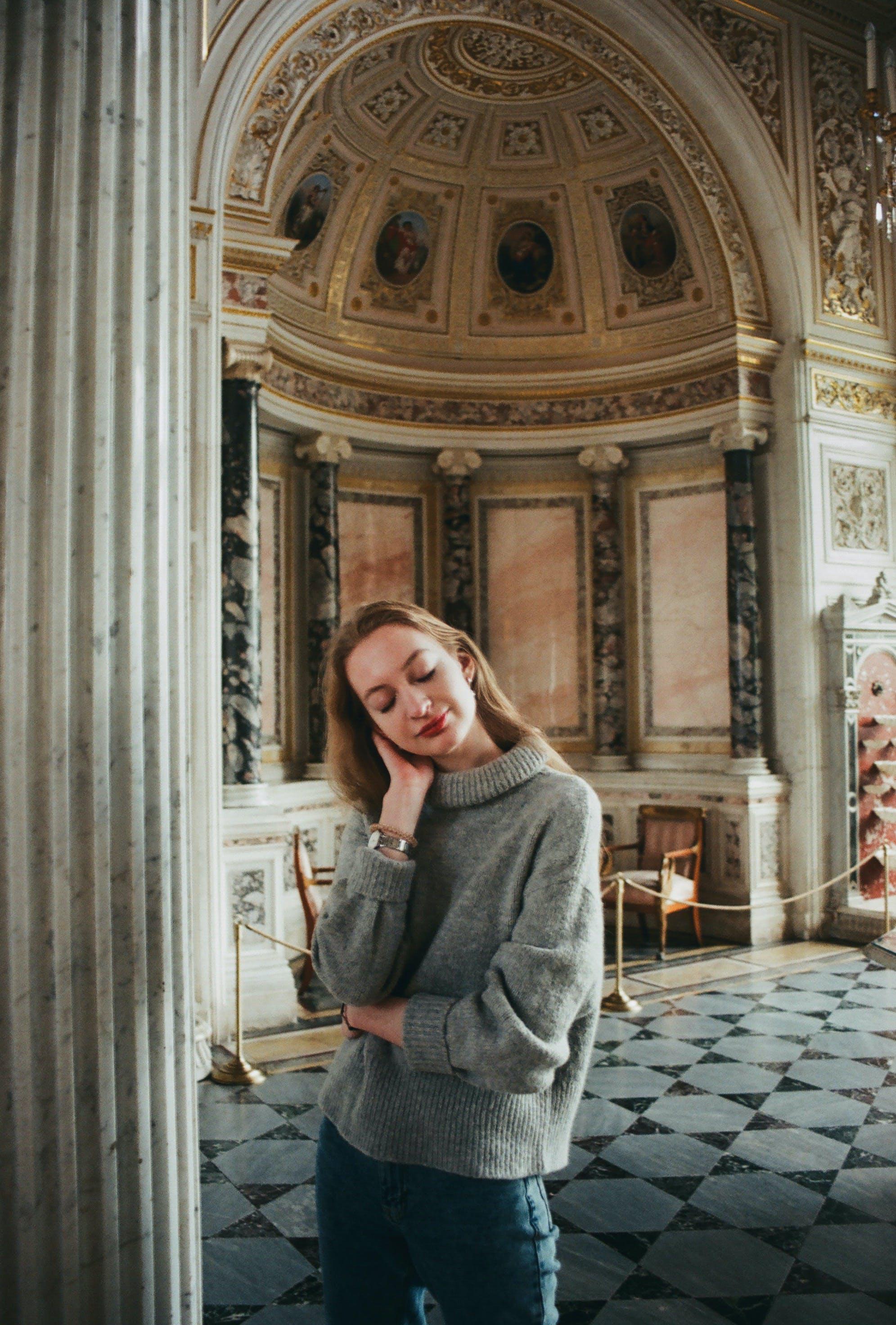 Woman in Gray Turtle-neck Sweater Near White Concrete Pillar