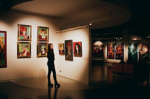 Woman Wearing Black Top Standing Near Paintings